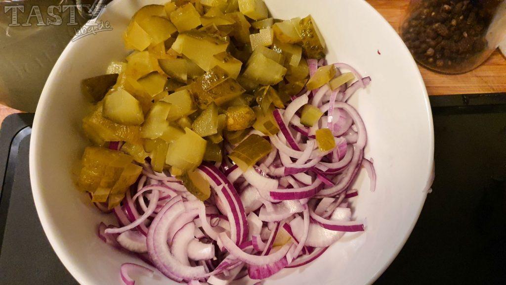 Zutaten für den berliner Wurstsalat werden kleingeschnitten.